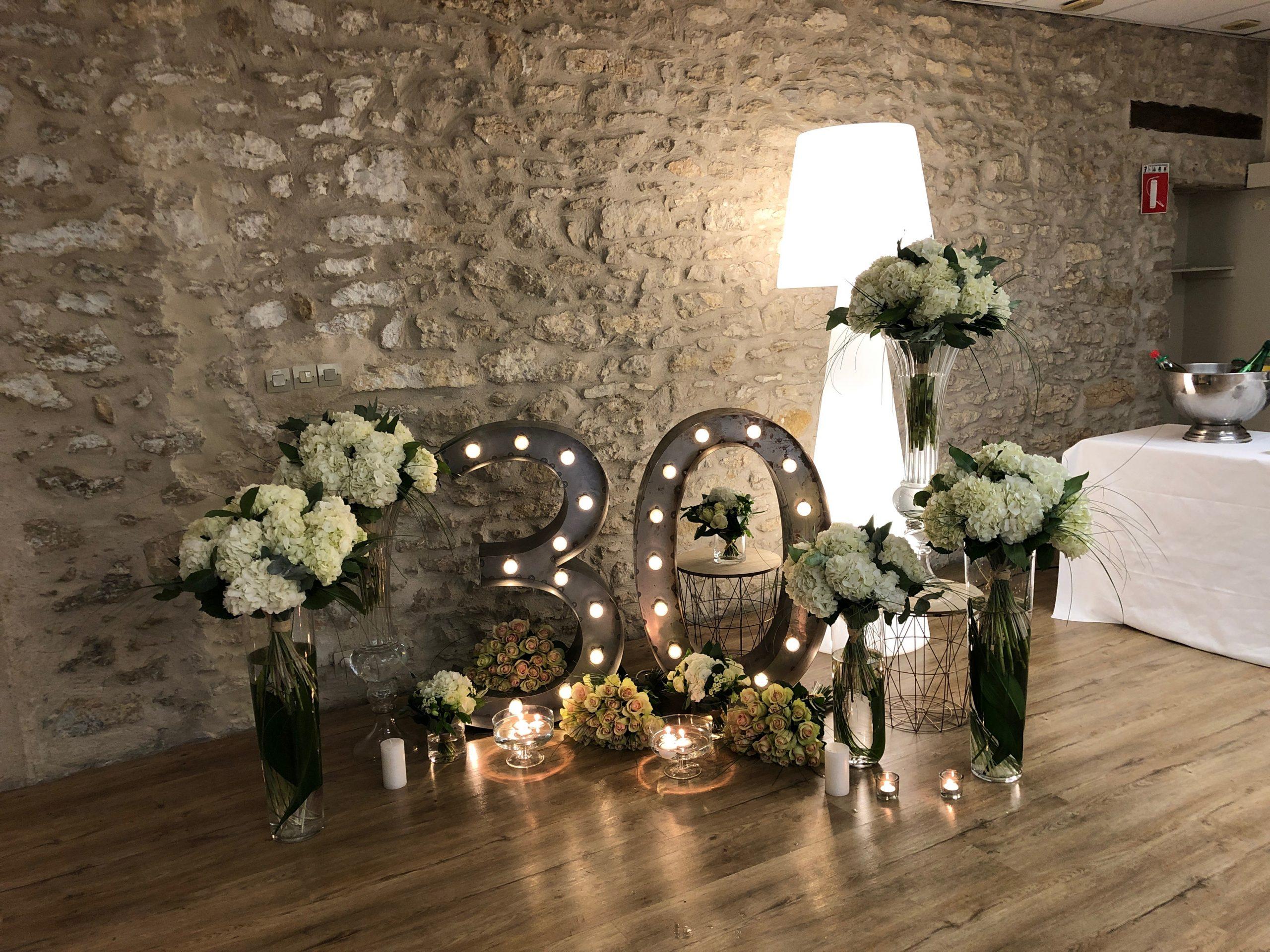 installation florale et lumineuse devant un mur de pierre